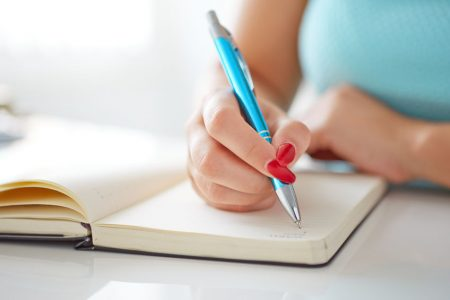 30502332 - young woman writes to black diary on a white table